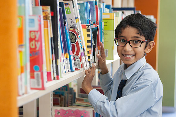 student looking through books in the school library