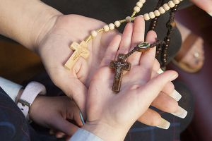 two hands with beige and brown rosary