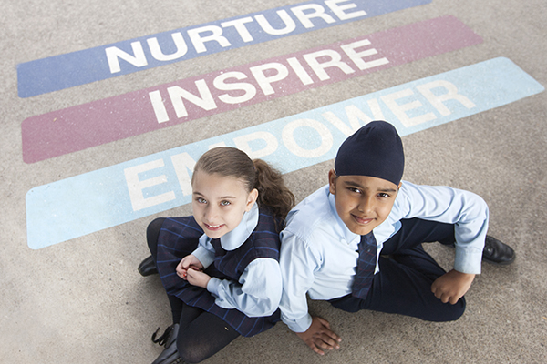 students sitting on school carpet with text Nurture, Inspire and Empower